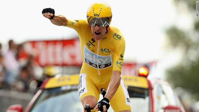 Bradley Wiggins punches the air as he crosses the finish line first on Saturday in the penultimate stage of the Tour de France