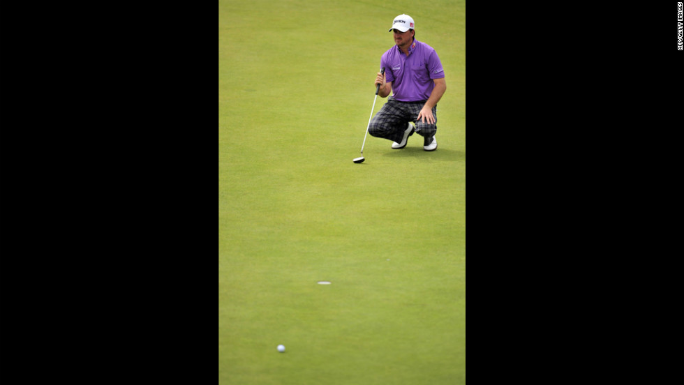 McDowell squats to line up a putt on the second green.