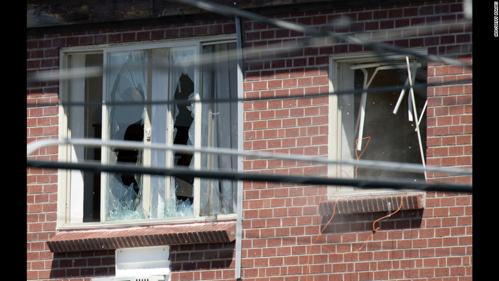Debris flies out a window, right, after law enforcement officers detonate an explosive device inside the apartment July 21, 2012.
