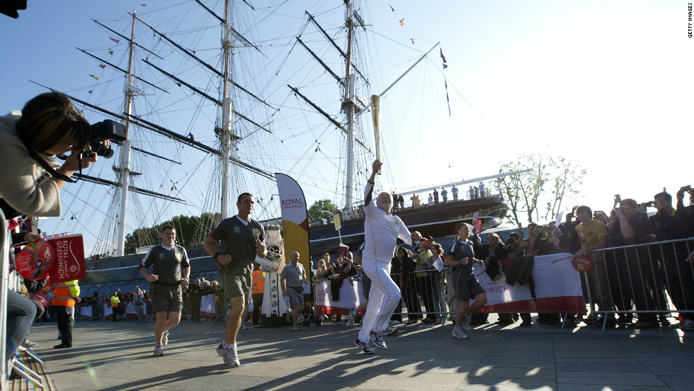 British sailor Sir Robin Knox-Johnston runs around the restored Cutty Sark ship with the London 2012 Olympic Torch in Greenwich, south London, on Saturday July 21.