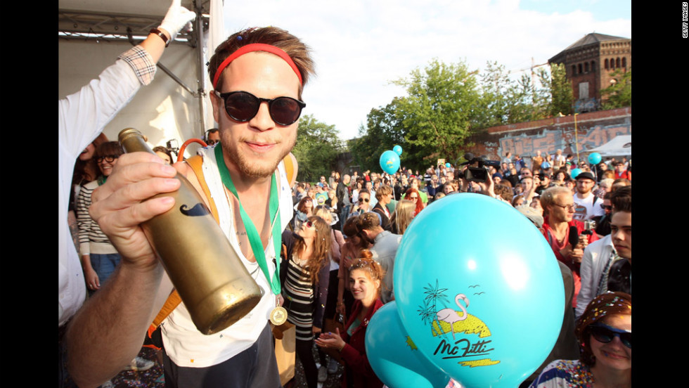 "A member of the winning team, Jam FM, holds the ""Golden Club Mate"" trophy after winning the second annual Hipster Olympics on Saturday, July 21, in Berlin. The games include horn-rimmed-glasses throwing, a vinyl- record-spinning contest, cloth tote sack races and glitter tossing. Click through the gallery to see the event."