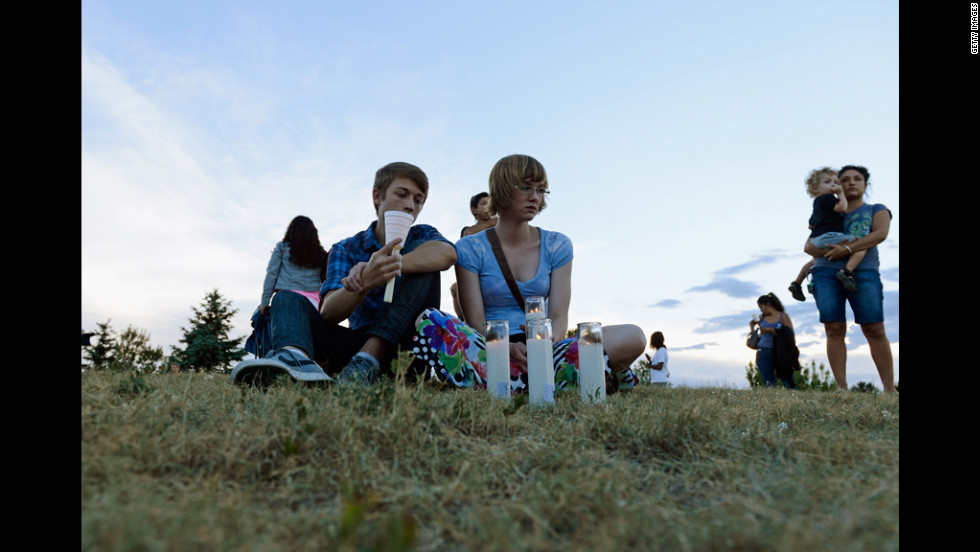 Nathan Mendoza, left, and Melissa Clark sit on the grass during a vigil.