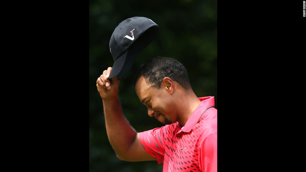 Woods tips his cap to the crowd on Sunday.