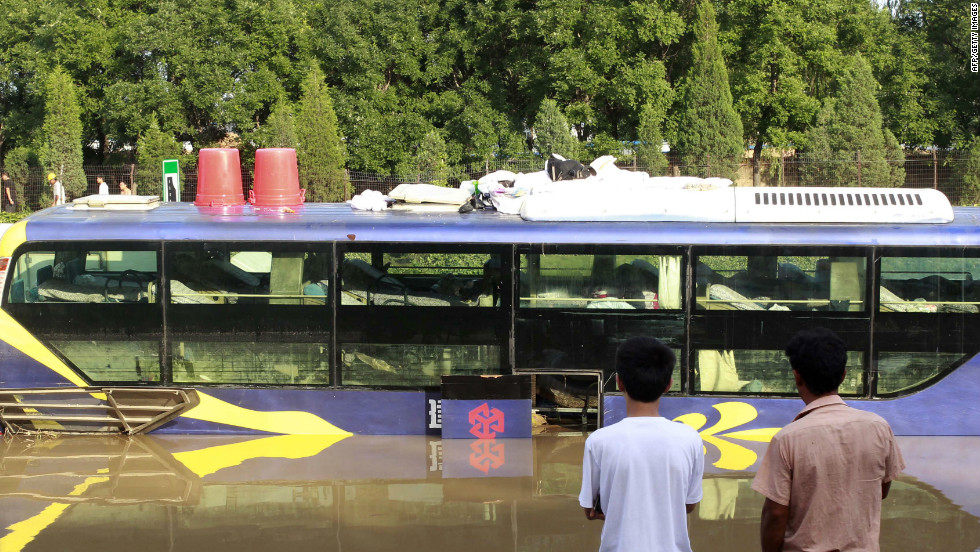 Two men watch as emergency services personnel try to retrieve a damaged bus which was submerged in a flooded carpark after a storm hit Beijing, July 22, 2012.