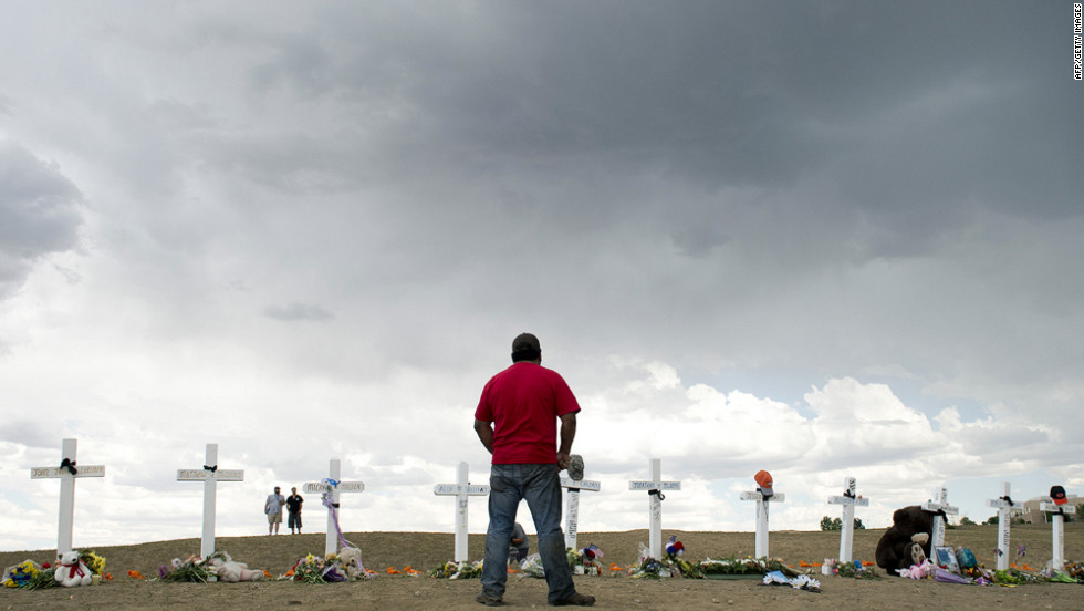 A man pauses before the crosses at the memorial near the Century 16 movie theater on Sunday.