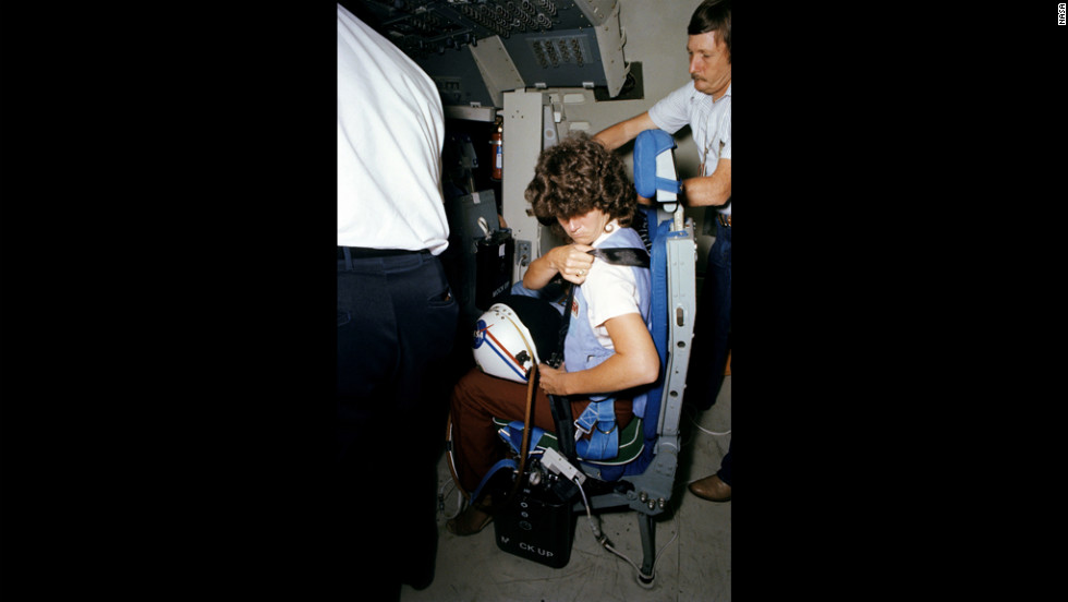 A technician helps Ride strap herself into a shuttle mission simulator in Houston in May 1983, less than a month before her launch.