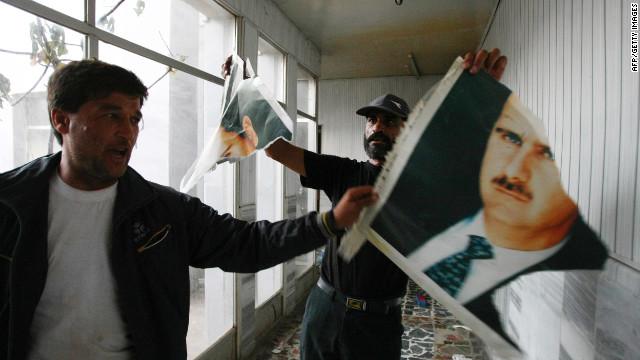 Free Syrian Army soldiers rip a portrait of President Bashar al-Assad at the Bab al-Salam border crossing to Turkey on Sunday.