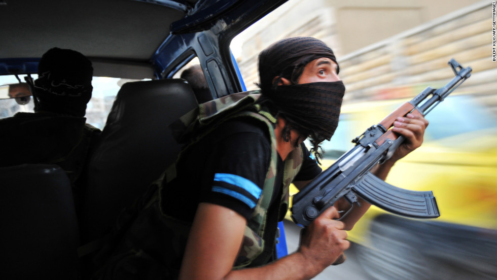 Syrian rebels hunt for snipers after attacking the municipality building in the city center of Selehattin on July 23, 2012.