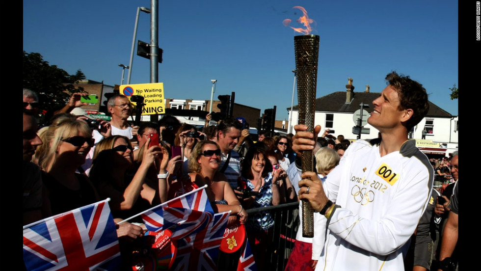 James Cracknell carries the Olympic flame on the torch relay leg through Kingston Upon Thames on Tuesday, July 24. The flame is traveling 2,875 kilometers (1,786 miles) through the United Kingdom over 70 days. Its journey ends Friday at the opening ceremony of the London 2012 Olympic Games.