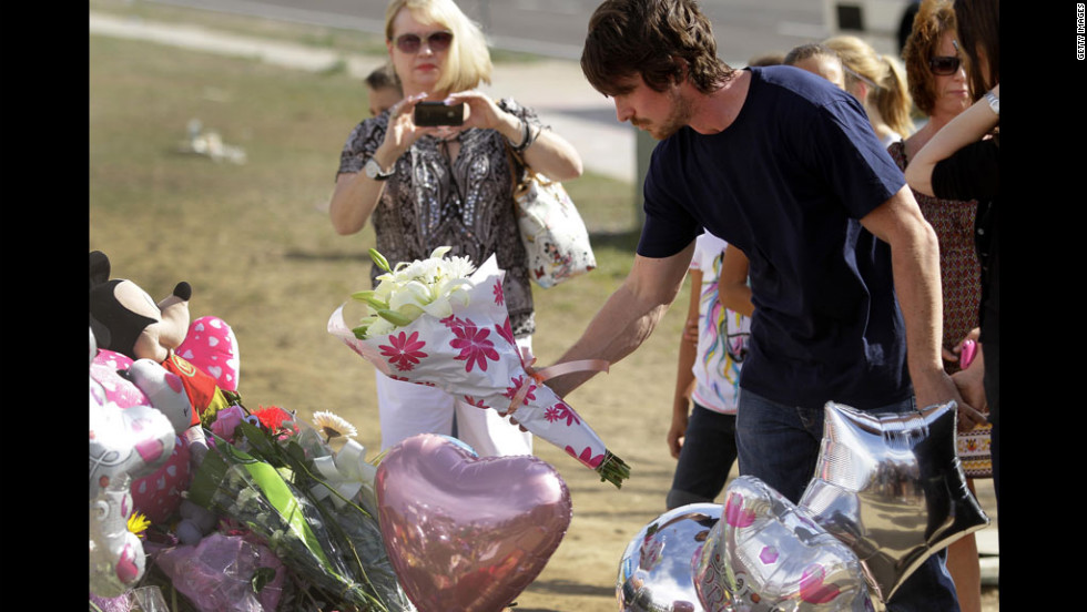 Bale places flowers at the memorial while other mourners look on.