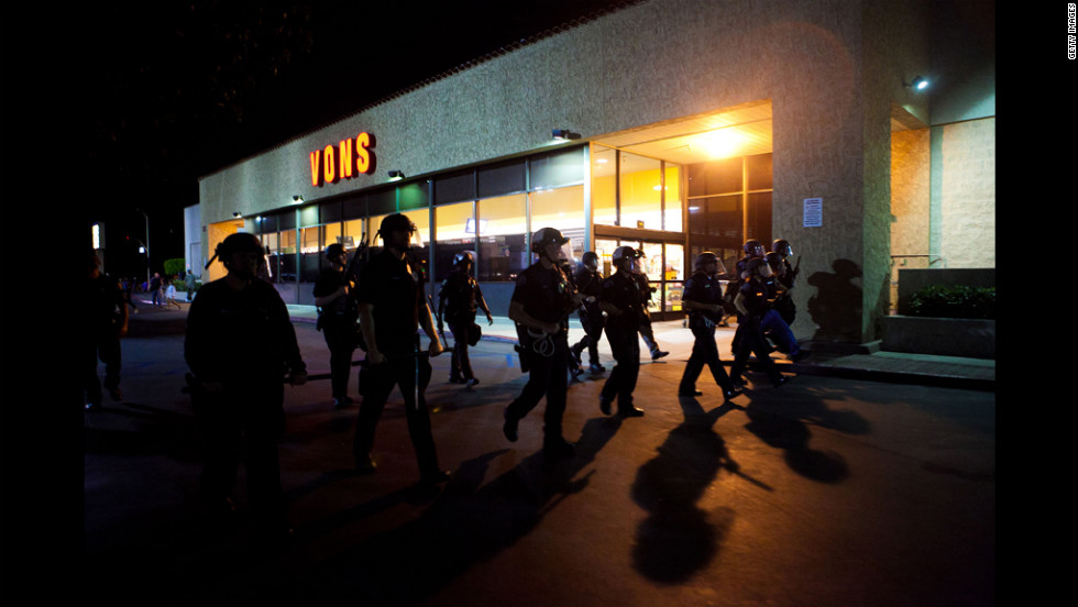 A line of officers moves through a shopping center.