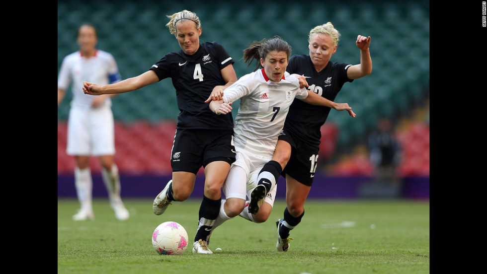 Katie Hoyle, left, of New Zealand and teammate Betsy Hassett challenge Karen Carney of Great Britain during their match in the first round of women's soccer in the London 2012 Olympic Games at Millennium Stadium on Wednesday, July 25, in Cardiff, Wales.