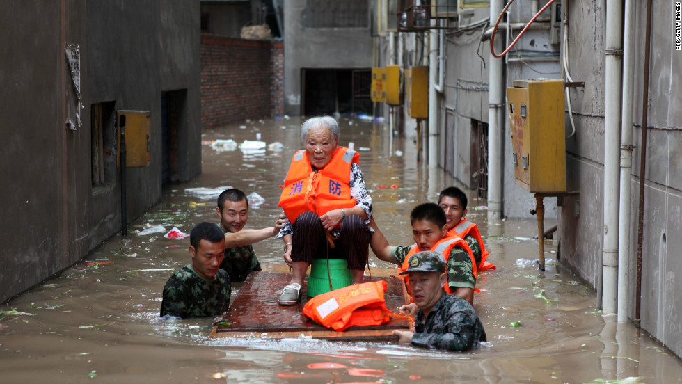 Rescuers evacuate an elderly woman from her flooded home in Chongqing, southwest China, July 23, 2012.
