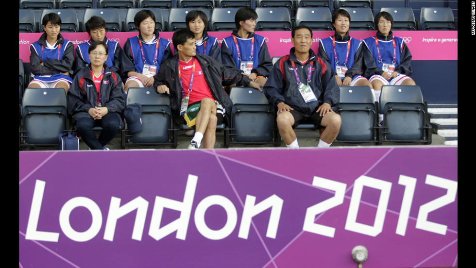 North Korean soccer coach Gun Sin Ui, at center in red shirt, waits for his team's match to begin at Hampden Park in Glasgow, Scotland, on Wednesday, July 25. The first-round match against Colombia was delayed.