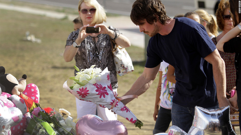 Bale places flowers at the memorial across the street from the Century 16 movie theater in Aurora.
