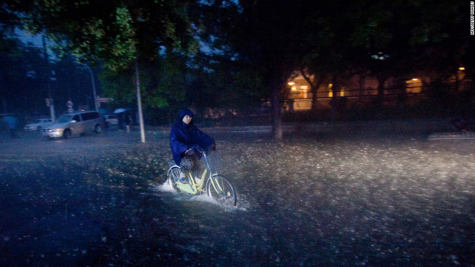 A cyclist rides through a flooded street in Beijing during heavy rainfall Saturday. More rain is forecast as Beijing cleans up after the weekend downpour.