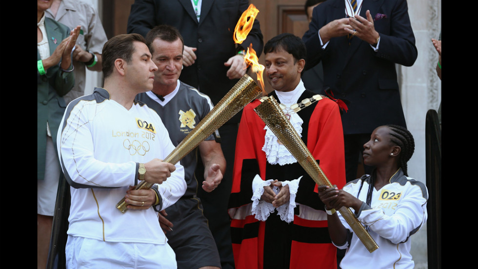 Torchbearer Rhyania Blackett-codrington, right, passes on the Olympic flame to comedian David Walliams, left, before setting off from Islington Town Hall July 26.