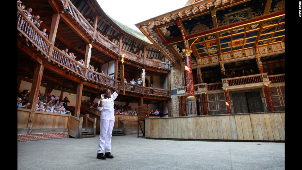 Torchbearer Ifeyinwa Egesi holds the Olympic flame inside the Globe Theatre in London on Thursday.