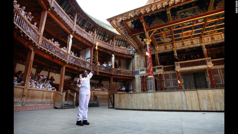 Torchbearer Ifeyinwa Egesi holds the Olympic flame inside the Globe Theatre in London on Thursday.