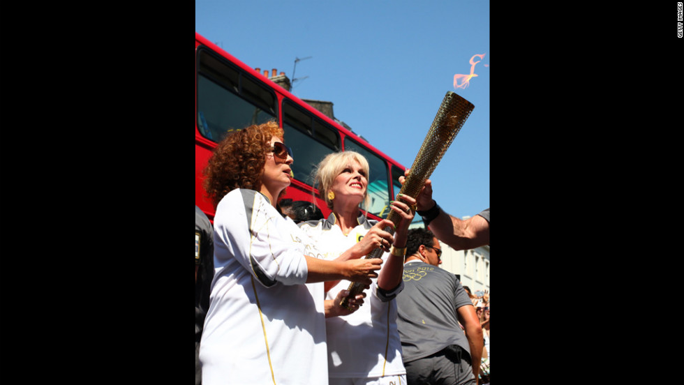 "Torchbearers Jennifer Saunders and Joanna Lumley, known for their ""Absolutely Fabulous"" characters Edina and Patsy, carry the Olympic flame through Lambeth, Kensington and Chelsea on Thursday,  July 26, in London."
