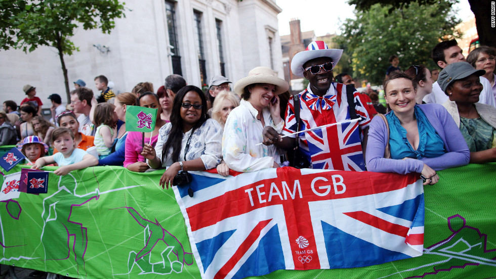 Spectators gather as the Olympic torch is carried from Islington Town Hall on Thursday. London cheered on the torch as it made its way past the city's historic landmarks.