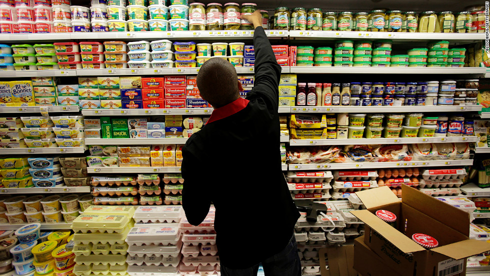 An employee stocks dairy products at a supermarket in New York on Wednesday, July 25. The U.S. Department of Agriculture said prices of dairy products like cheese, milk and eggs are expected to rise 2% to 3% because of the drought.