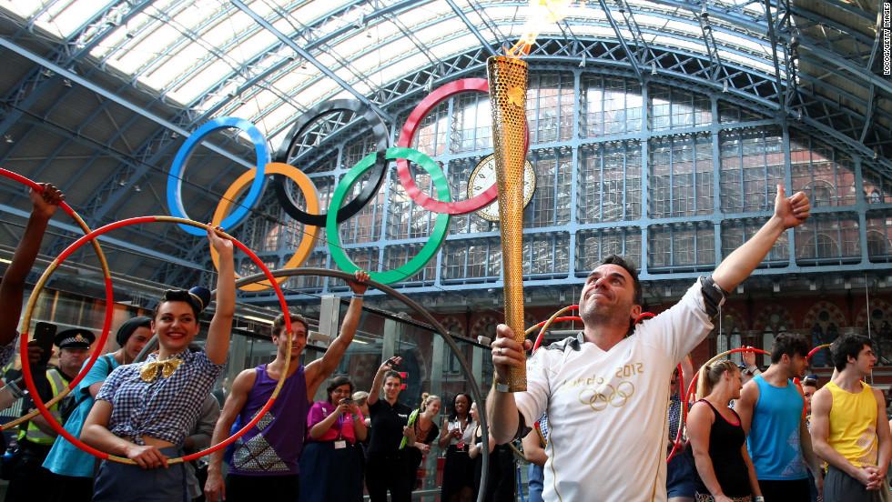 Torchbearer Daniel Mccubbin holds the Olympic flame inside St. Pancras International Railway Station on Thursday, July 26.