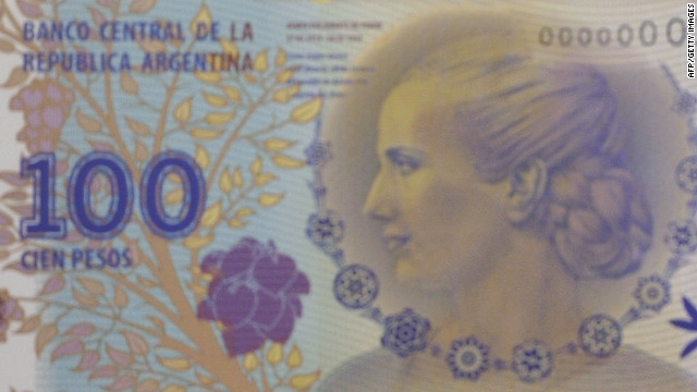 Argentine President Cristina Kirchner, left, shows the new 100 pesos bill featuring created by French graphic artist Roger Pfund