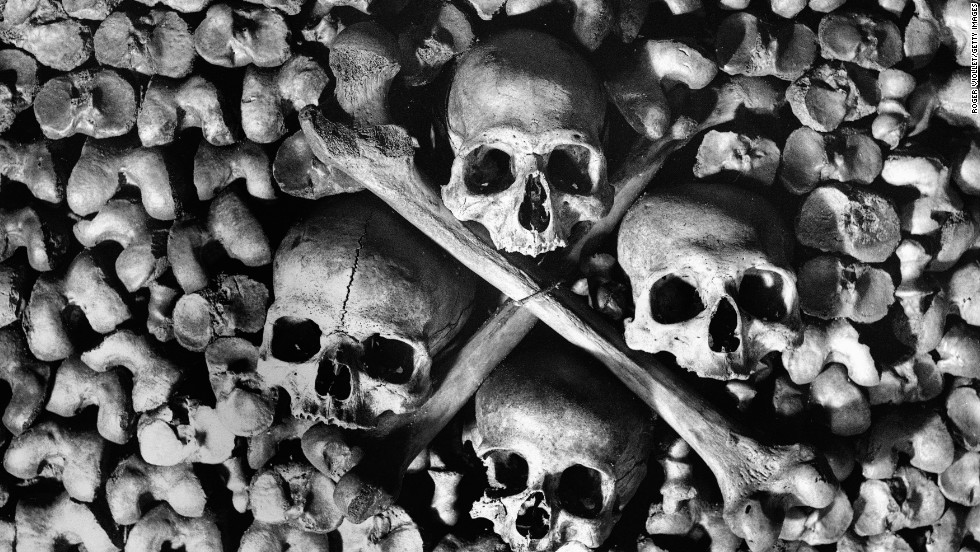 Skulls and bones are arranged to form the walls of the tunnels in the Paris Catacombs. Circa 1900.