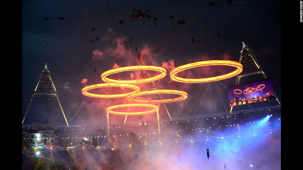 "Freshly ""forged"" Olympic Rings fly above the chimneys during The Age of Industry scene."