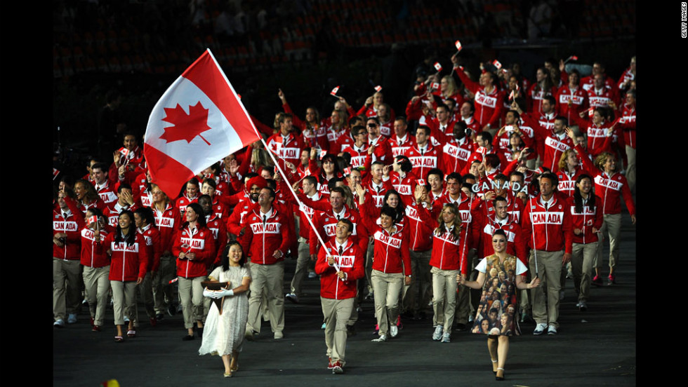 Simon Whitfield of the Canada Olympic triathlon team carries his country's flag.