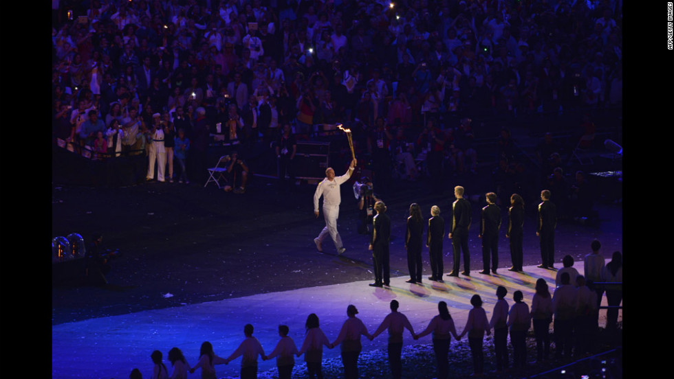 Five-time Olympic rowing gold medalist Steve Redgrave of Britain carries the torch during the opening ceremony and then hands it off to a group of young athletes.