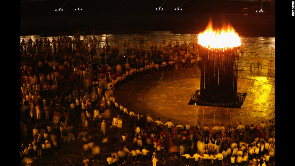 Participants look on as the Olympic flame burns in the cauldron.