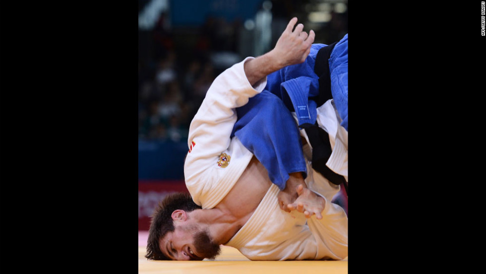 Musa Mogushkov of Russia, in white, competes with Azerbaijan's Tarlan Karimov, in blue, during their men's 66 kilogram judo event.