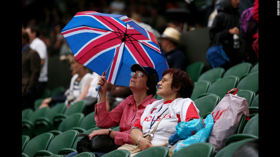 Fans at Wimbledon's Centre Court take shelter from a downpour under a Union Jack umbrella during a rain delay.