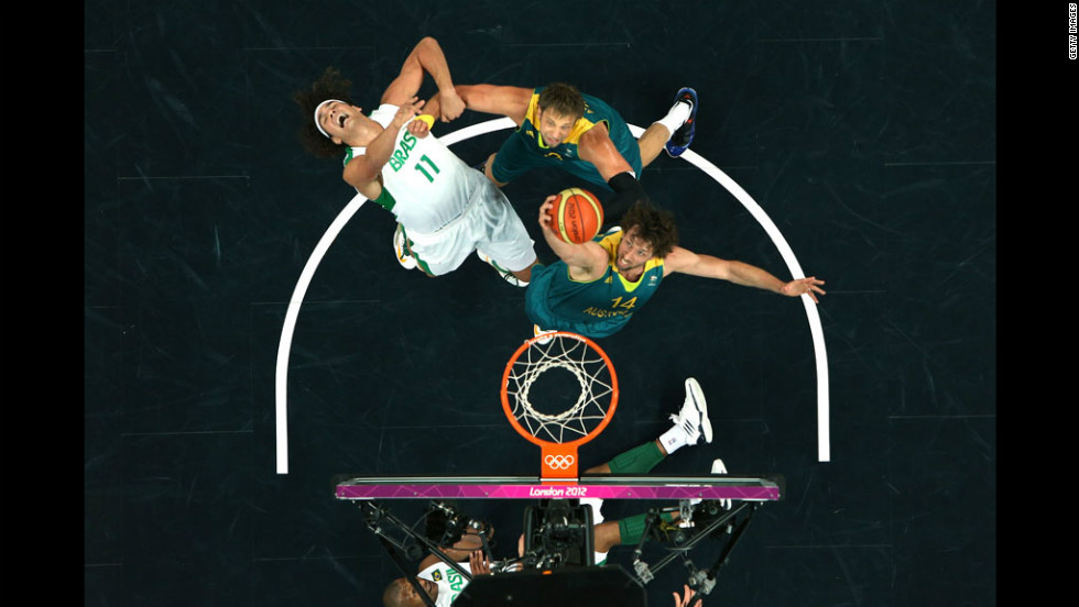 Brazil's Anderson Varejao, No. 11 in white, gets fouled by Australia's David Andersen, No. 13, as Anderson teammate Matt Nielsen goes for the rebound during the Brazil-Australia men's basketball game.