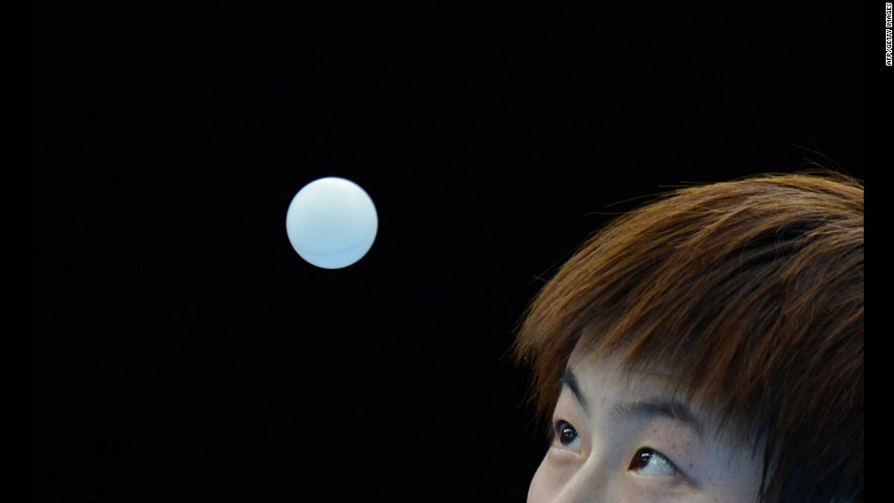 Ding Ning of China serves to Jiang Huajun of Hong Kong during a table tennis women's single round match on Monday.