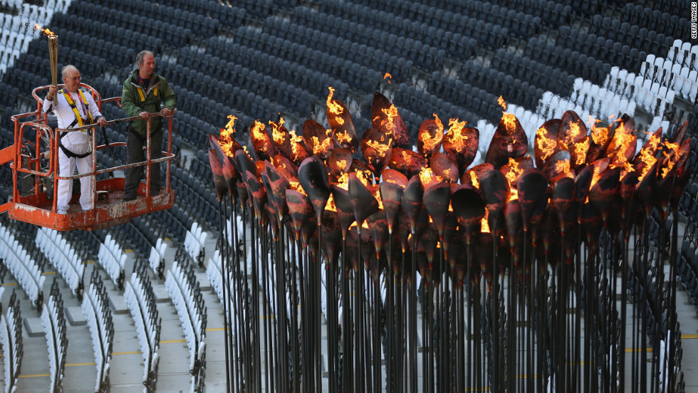 Austin Playfoot lights the cauldron after it was moved into position, ready for the events in Olympic Stadium, on Monday, July 30, in London.
