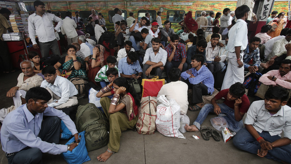 Passengers sit on the platform at train station in New Delhi on Tuesday.