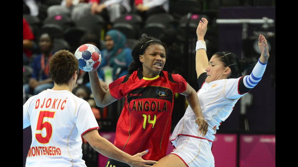 Angola's Natalia Bernardo, center in red, vies with Montenegrin players during a women's preliminary handball match.
