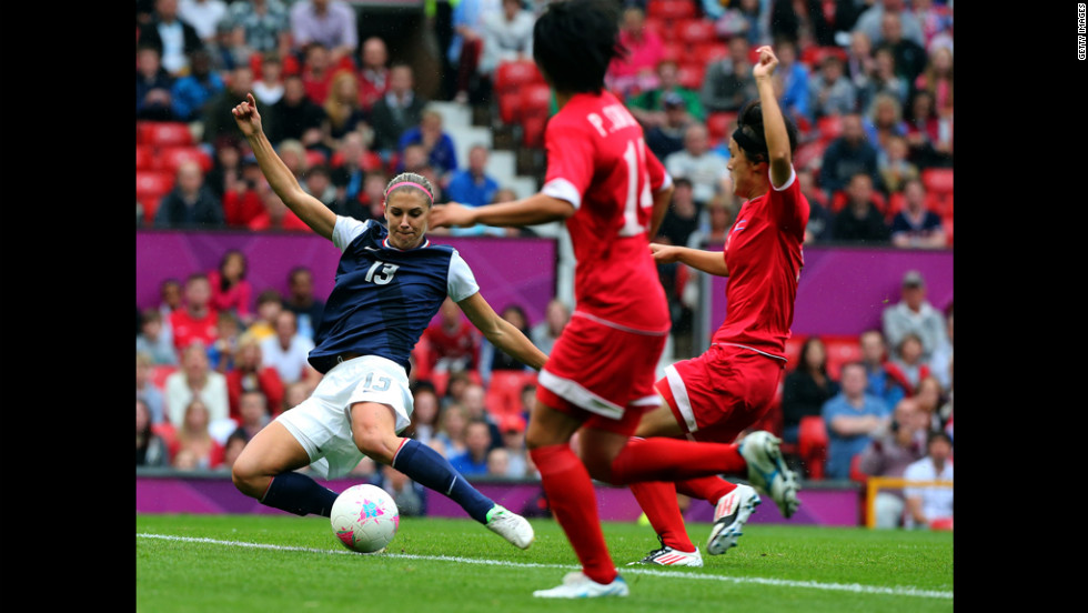 Alex Morgan of the United States strikes the ball while Kim Myong Gum and Pong Son Hwa of North Korea attempt to deflect during the women's soccer first-round match.