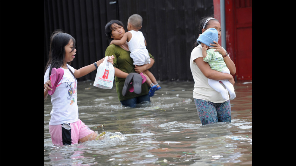 People wade through a flooded street Wednesday in Navotas, a Manila suburb.
