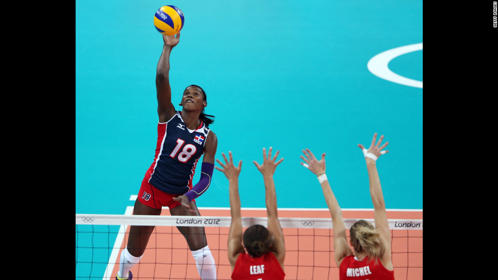 Bethania de la Cruz de Pena, left, of  the Dominican Republic spikes the ball as Britain's Savanah Leaf, center, and Ciara Michel defend during women's volleyball action.