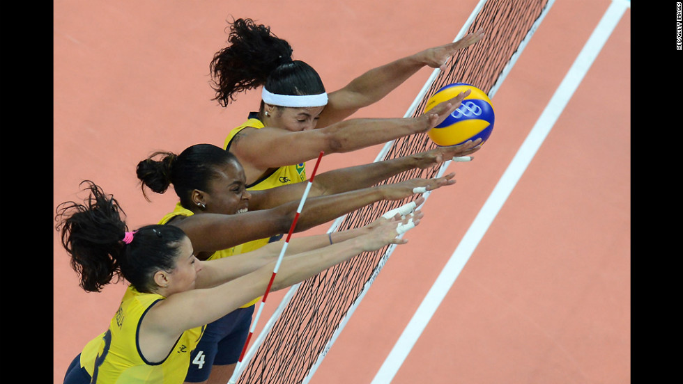 From left, Brazil's Sheilla Castro, Fabiana Claudino and Paula Pequeno attempt to block during a women's preliminary pool volleyball match between Brazil and China.