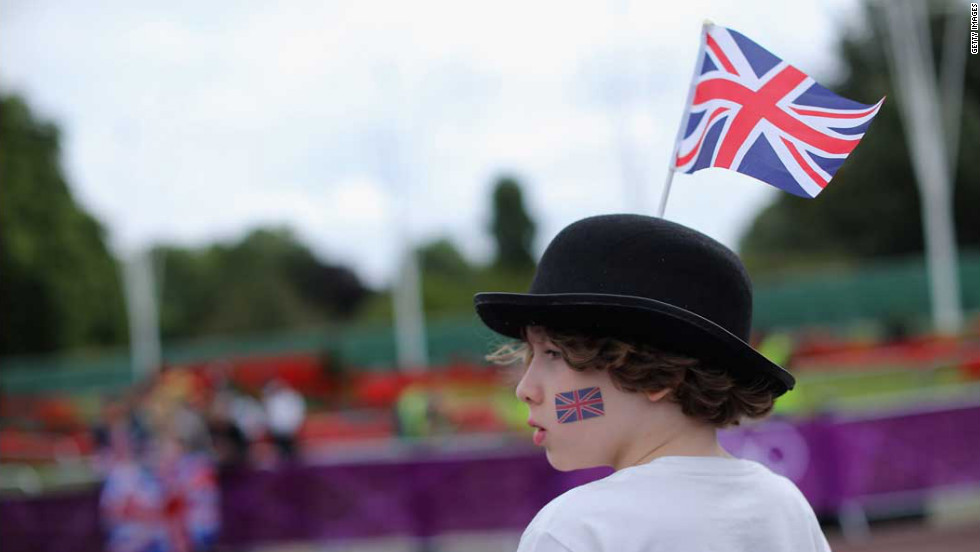 A boy watches as athletes make their way past Buckingham Palace while competing in the cycling leg of the women's triathlon at Hyde Park.