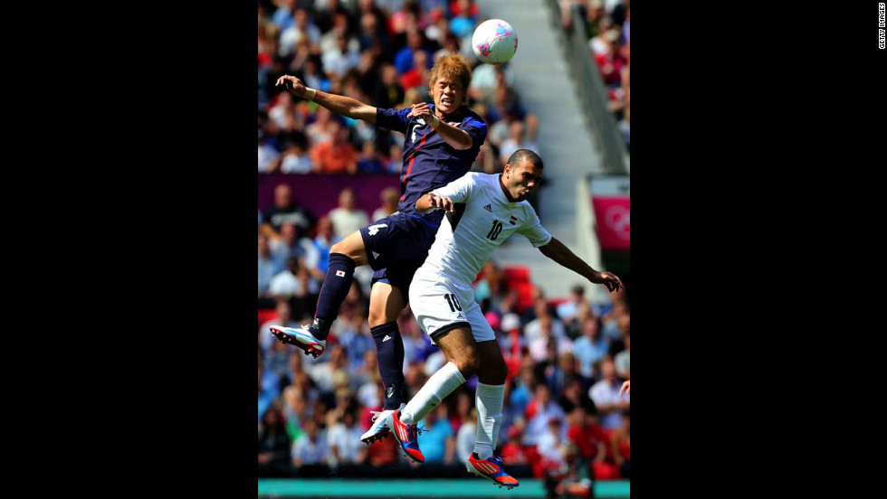 Hiroki Sakai of Japan clashes with Emad Moteab of Egypt to score during the men's football quarterfinal match at Old Trafford in Manchester, England.