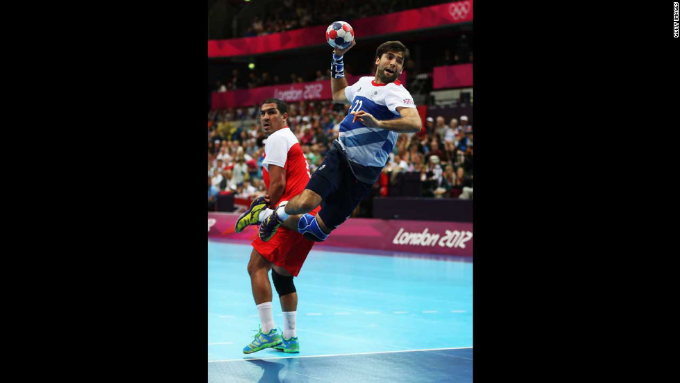 Robin Garnham of Great Britain shoots past Issam Tej of Tunisia during a men's handball preliminaries match in group A.