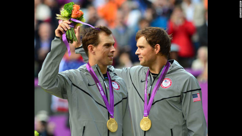 Mike Bryan, left, and Bob Bryan pose on a podium with their gold medals after winning the men's doubles tennis tournament.