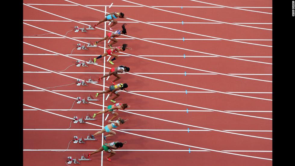 Athletes start in the women's 100-meter semifinal at Olympic Stadium.