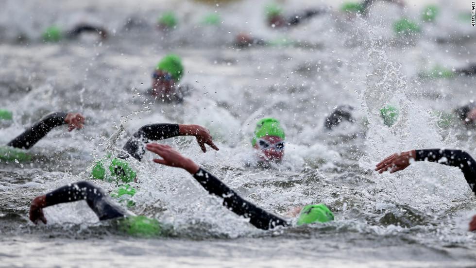 Athletes swim the first leg of the women's triathlon during Saturday.